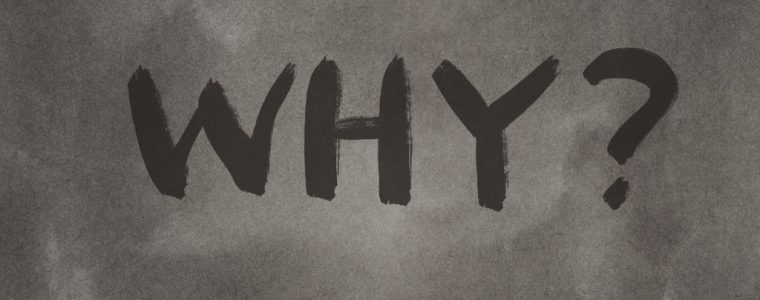 The word 'why' written on a blackboard.