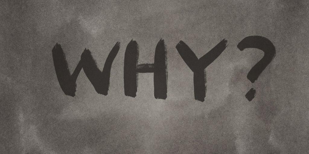 The word 'why' written on a blackboard.
